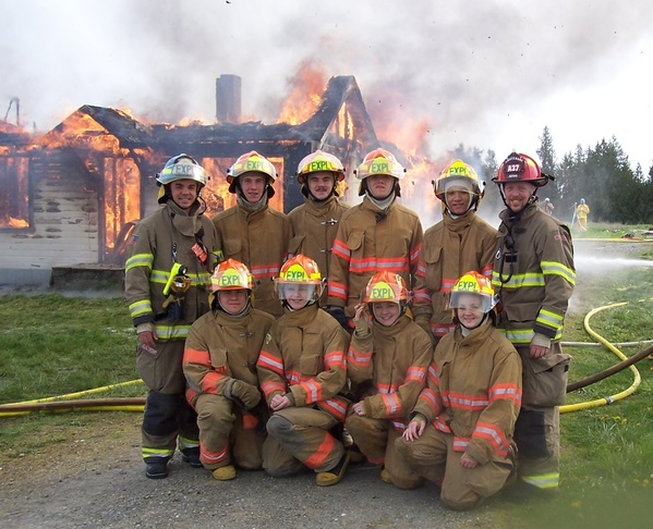 Explorer Scout Post 1003 posed in front of burning house during firefighter experience training