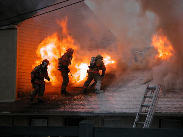 Three firefighters very near blaze on roof of burning building