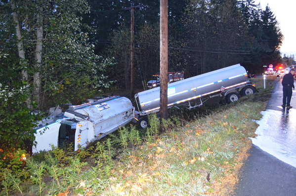 Overturned semi-truck and trailer in ditch with hazardous material spill