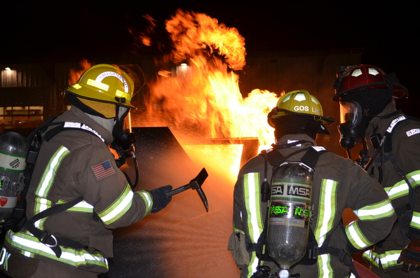 Three firefighters with full gear battling a large fire during volunteer training