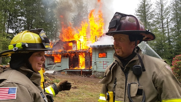 Two firefighters talking in front of burning house during volunteer training